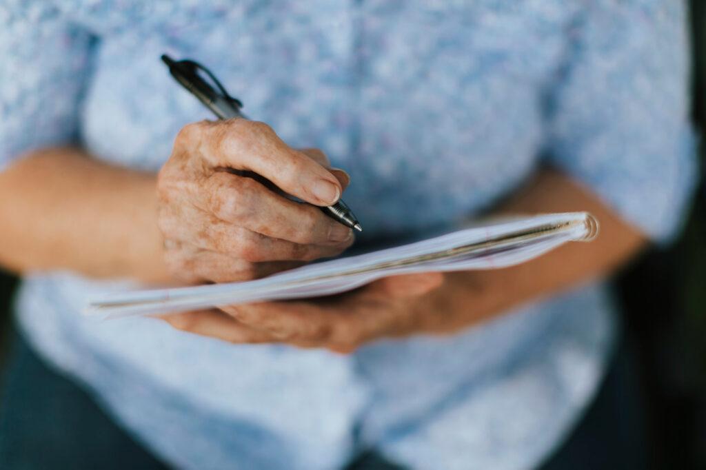 Pessoa idosa escrevendo em um caderno